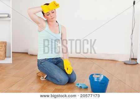 Pretty Red-haired Woman Having A Break While Cleaning The Floor