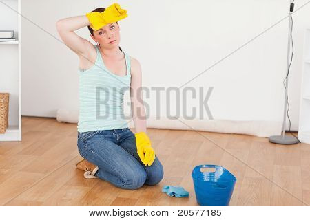 Cute Red-haired Woman Having A Break While Cleaning The Floor