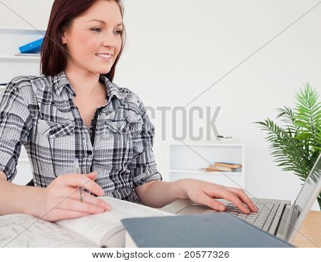 Young Attractive Red-haired Girl Relaxing With A Laptop While Studying