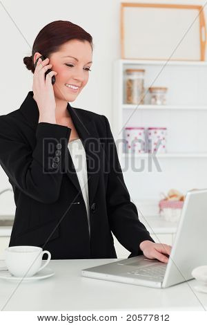 Attractive Red-haired Woman In Suit Relaxing With Her Laptop While Phoning In The Kitchen