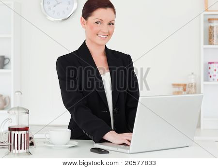 Pretty Red-haired Woman In Suit Relaxing With Her Laptop While Posing In The Kitchen