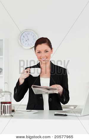 Attractive Red-haired Woman In Suit Reading The Newspaper While Having Her Breakfast In The Kitchen