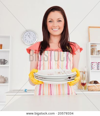 Good Looking Red-haired Woman Posing While Holding Some Dirty Plates In The Kitchen