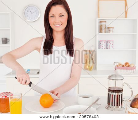 Young Gorgeous Red-haired Woman Cutting An Orange In The Kitchen