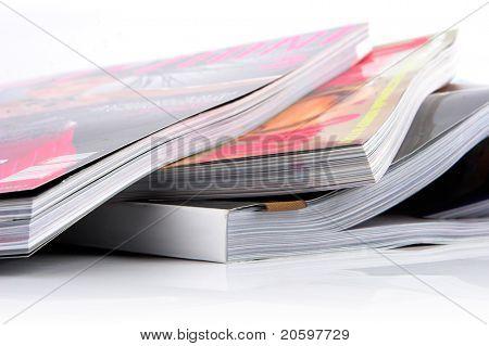Pila de revistas brillante sobre un fondo blanco.