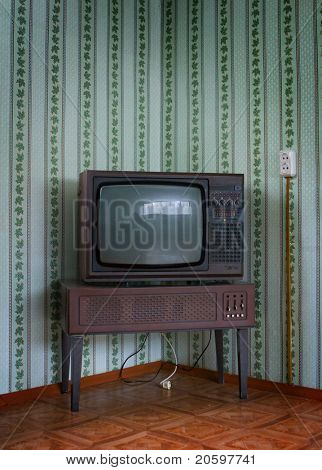 Retro grunge tv against wallpaper wall.