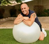 stock photo of senior men  - man relaxing after working out with an exercise ball on lawn outside - JPG