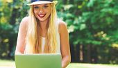 Young woman using her laptop outside on a beautiful summer day