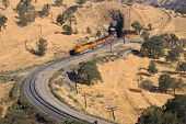pic of bnsf  - Diesel electric locomotives drag their train up Tehachapi Mountain California - JPG