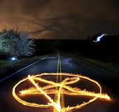 picture of pentacle  - Pentagram made of fire flames in the middle of a country rural road at night time - JPG