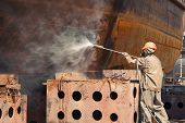 foto of decontamination  - Man in chemical protection suit against radiation disinfects surface - JPG
