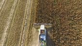 Harvester Harvests Corn. Collect Corn Cobs With The Help Of A Combine Harvester. Ripe Corn On The Fi poster