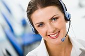 stock photo of telemarketing  - Portrait of friendly smiling female negotiator with marvelous blue eyes - JPG