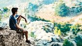 Man on top of the world, teen guy sits on the edge of a cliff and enjoying amazing view of the wild  poster