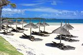 stock photo of mauritius  - Tourist resort beach with umbrellas and chairs in Mauritius island - JPG