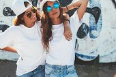 Two models wearing plain white t-shirts and hipster sunglasses posing against street wall. Teen urba poster