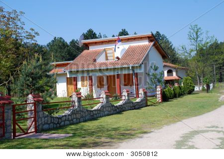 House With Stone Fence And Serbian Flag