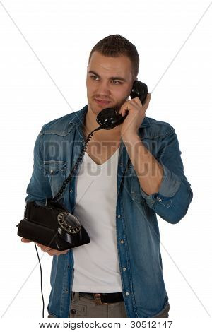 Young Man Making A Phone Call With An Old Telephone Against A White Background