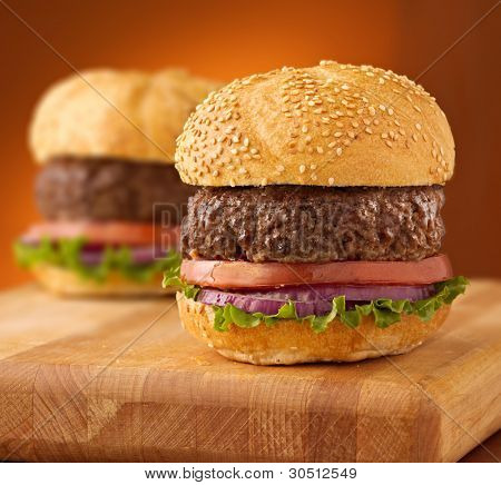 Hamburgers on wooden board on an orange vignetted background.