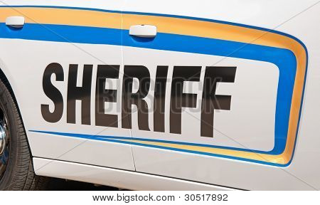 Sheriff text in black on side of a white patrol car, lined with yellow and blue decal stripes