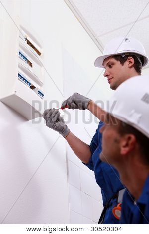 Two electrical workers installing fuse box