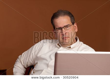 Scowling Middle Age Man At Computer