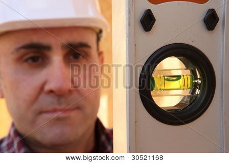 Builder knelt holding spirit level