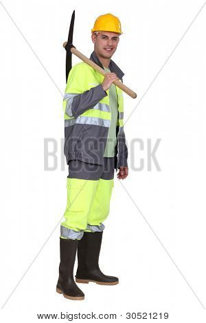 portrait of bricklayer standing with pickaxe over his shoulder