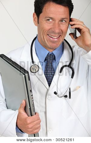 A doctor holding a laptop and having a conversation via his mobile phone.