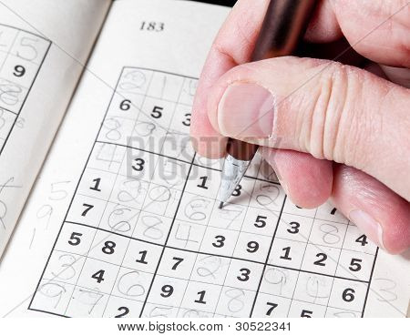 Man Hand Holding Pencil On Sudoku Puzzle