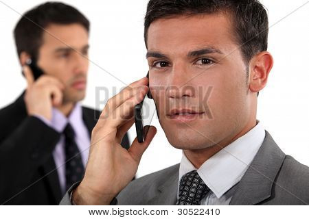 Businessmen talking on their mobile phones
