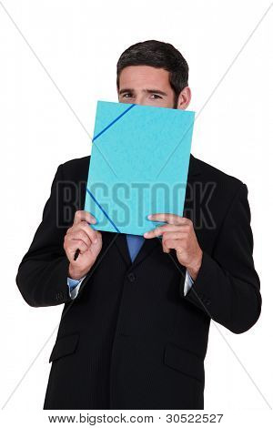 Smiling man hiding behind a folder