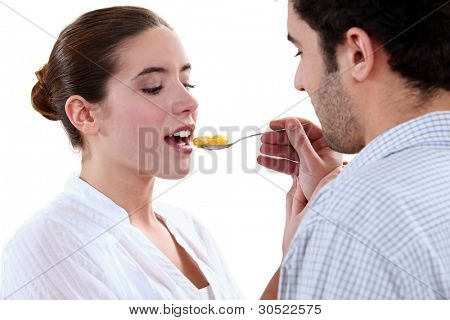boyfriend feeding his girlfriend with a spoon