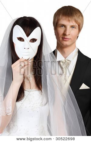 Beautiful bride hid her face behind white mask; groom stands behind her isolated on white background; focus on woman
