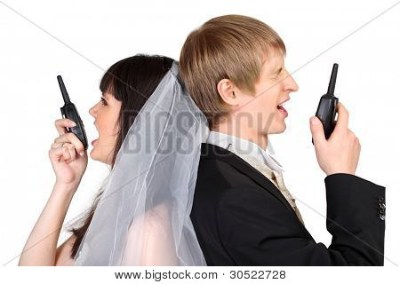 Young groom and bride shout on radio isolated on white background; focus on man