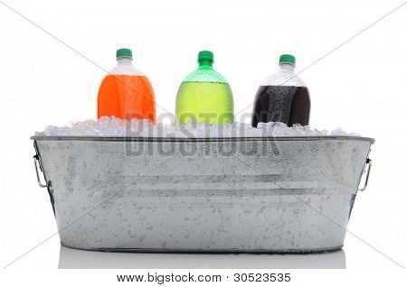 Party bucket filled with ice and three two liter soda bottles. Orange, lemon lime and cola plastic bottles with condensation in horizontal format over a white background and reflection.