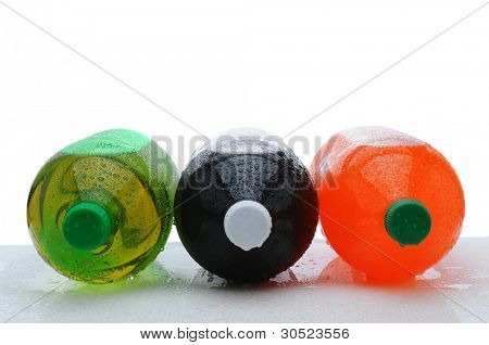 Three plastic two liter soda bottles laying on their sides with condensation on a wet counter. Horizontal format over a white background.