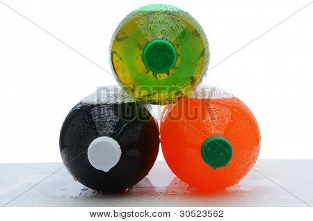 Three plastic two liter soda bottles laying on their sides stacked in pyramid shape with condensation on a wet counter. Horizontal format over a white background.