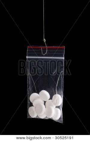 Tablets on fish hook isolated on black