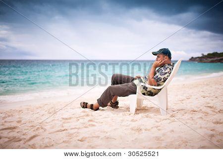 Pensive sitting man near the beachfront