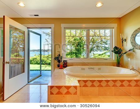 Yellow Bathroom With Lake View And Large Tub.