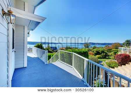 Front Door Porch With Water View And Grey House And Bush Greenery.