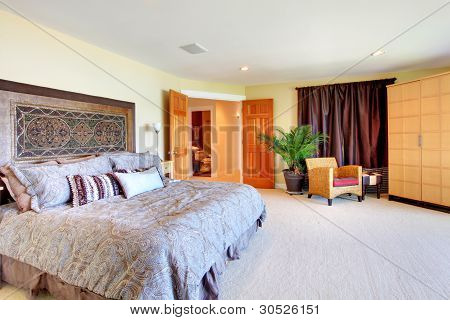 Large Yellow Master Bedroom With Open Doors And Huge Bed.