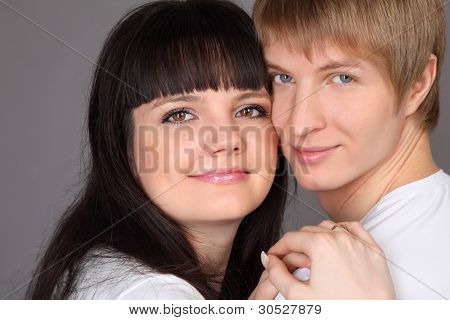 Happy man and woman dressed in white shirts on gray background