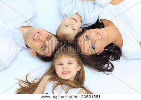 Familia feliz, madre, padre e hija descansando en la cama blanca