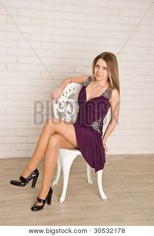 An Attractive Young Woman Sitting On White Chair In A Lovely Dress.