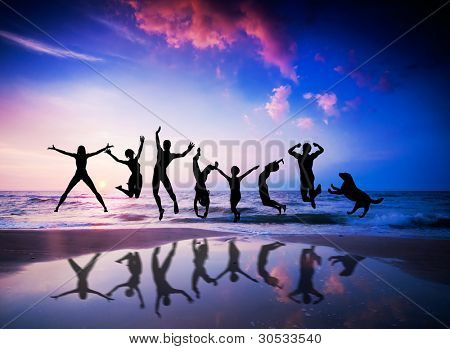 Happy people and dog jumping together on the sunset beach