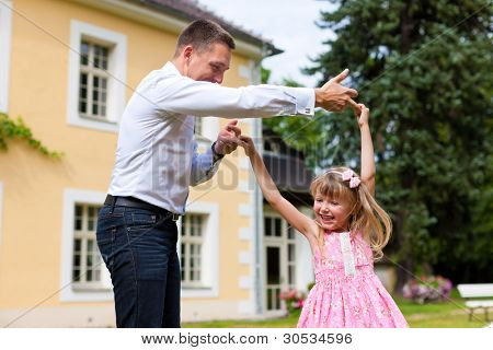 Family affairs - father and daughter playing in summer; he is dancing with her in the garden in front of the house