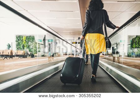 poster of Woman Traveller With Travel Suitcase Or Luggage Walking In Airport Terminal Walkway For Vacation Tra