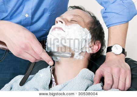 Man, relaxing in a barbers chair, being shaved